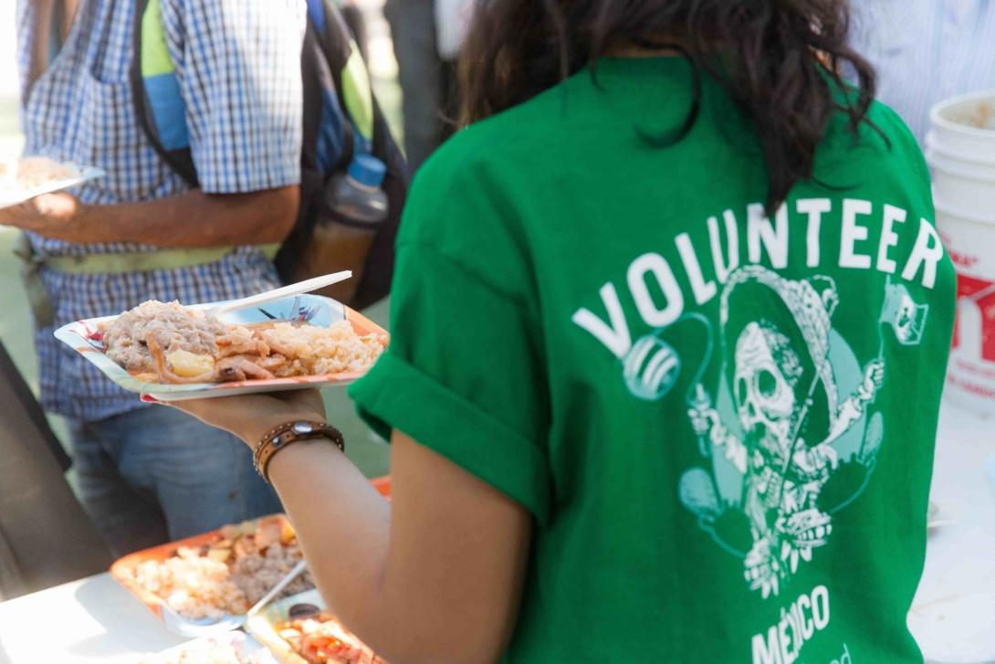Voluntaria sirviendo comida a migrantes en un refugio en México.